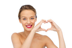 Smiling young woman showing heart shape hand sign. Beauty, people, love, valentines day and make up concept - smiling young woman with pink lipstick on lips Royalty Free Stock Photography