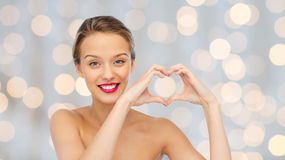 Smiling young woman showing heart shape hand sign Royalty Free Stock Images