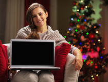 Smiling young woman showing laptop blank screen Royalty Free Stock Images