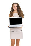 Smiling young woman showing laptop blank screen. Isolated on white Royalty Free Stock Image