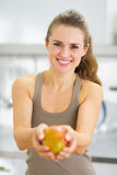 Smiling young woman showing mango Stock Photography