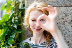 Smiling young woman showing OK sign and looking at camera Royalty Free Stock Photography