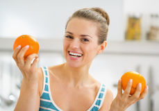 Smiling young woman showing oranges in kitchen Royalty Free Stock Photos