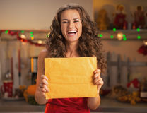 Smiling young woman showing package in kitchen Stock Photography