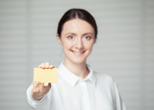 Smiling young woman showing a plastic golden card Stock Photos