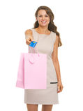 Smiling young woman showing shopping bag and credit card Royalty Free Stock Images