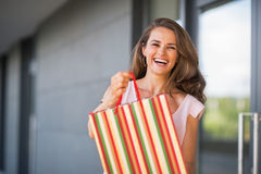 Smiling young woman showing shopping bag Royalty Free Stock Photography