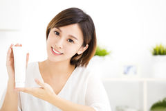 Smiling young woman showing skincare products Royalty Free Stock Photo