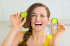 Smiling young woman showing slices of cucumber Stock Photography