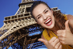 Smiling young woman showing thumbs up in front of Eiffel tower. Touristy, without doubt, but yet so fun. smiling young woman showing thumbs up in the front of Stock Images