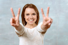 Smiling young woman showing two fingers Royalty Free Stock Images