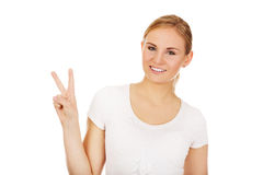 Smiling young woman showing the victory sign Royalty Free Stock Photography