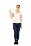 Smiling young woman showing the victory sign Stock Image