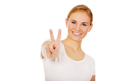 Smiling young woman showing the victory sign Stock Images