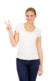 Smiling young woman showing the victory sign Royalty Free Stock Photo