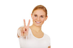 Smiling young woman showing the victory sign Stock Photography