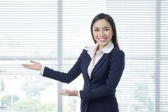 Smiling young woman shows something stock photography