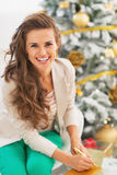 Smiling young woman singing envelope in front of christmas tree Royalty Free Stock Photos