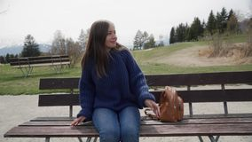 Smiling young woman sits on a wooden bench with amazing view over lake and mountains and relaxed on sunny spring day. Woman enjoying a picturesque place. 4k stock footage