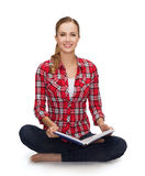 Smiling young woman sittin on floor with book Royalty Free Stock Photo