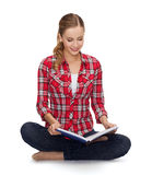 Smiling young woman sittin on floor with book Stock Photography