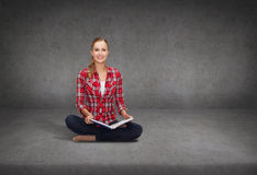 Smiling young woman sittin on floor with book Royalty Free Stock Photography