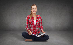 Smiling young woman sittin on floor with book Royalty Free Stock Images