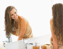 Smiling young woman sitting in bathroom and looking in mirror. Smiling young woman sitting with wet hair in bathroom and looking in mirror stock images