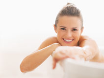 Smiling young woman sitting in bathtub Royalty Free Stock Photography