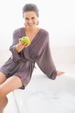 Smiling young woman sitting on bathtub and giving apple Stock Photography