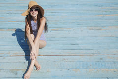 Smiling young woman sitting on the beach. Smiling attractive young woman sitting on the beach on the brigh background Royalty Free Stock Photos