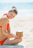 Smiling young woman sitting on beach with coconut Stock Photos