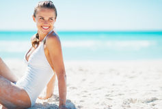 Smiling young woman sitting on beach and looking on copy space stock images
