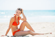 Smiling young woman sitting on beach Stock Photography