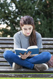 Smiling young woman sitting on bench and reading book, outdoor. Royalty Free Stock Images