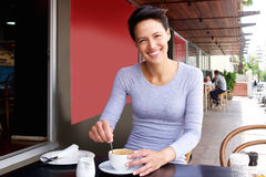 Smiling young woman sitting at cafe enjoying coffee Royalty Free Stock Images