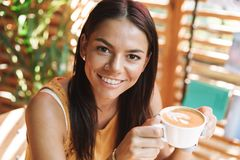 Smiling young woman sitting at the cafe. Indoors, drinking coffee stock image