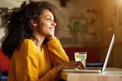 Smiling young woman sitting in a cafe with laptop Stock Images