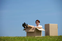 Smiling young woman sitting in cardboard box Stock Photography
