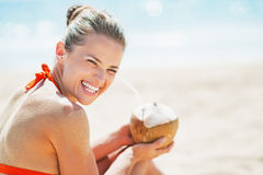 Smiling young woman sitting with coconut on beach Royalty Free Stock Images
