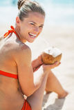 Smiling young woman sitting with coconut on beach Stock Photo