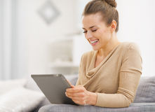 Smiling young woman sitting on couch and working on tablet pc royalty free stock photos