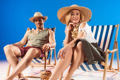 Smiling young woman sitting in deck chair by man and stack of pancakes stock photography