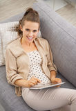 Smiling young woman sitting on divan and using tablet pc Royalty Free Stock Photos