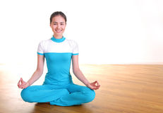 Smiling young woman sitting doing yoga lotus pose. Smiling young woman sitting and doing yoga lotus pose on parquet wooden floor Stock Photos