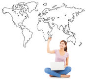 Smiling young woman sitting and drawing global map Royalty Free Stock Images