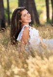 Smiling young woman sitting in a field in nature Stock Photos