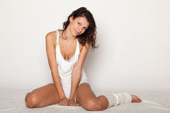 Smiling young woman sitting on floor Stock Photos