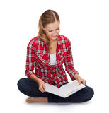 Smiling young woman sitting on floor with book Royalty Free Stock Image