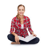 Smiling young woman sitting on floor with book Stock Photo